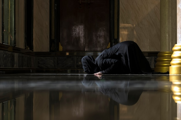 Muslim women wearing black shirts doing prayer according to the principles of islam. Premium Photo