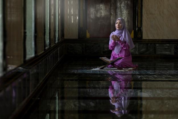 Muslim women wearing purple shirts doing prayer according to the principles of islam. Premium Photo
