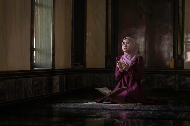 Muslim women wearing purple shirts doing prayer of islam. Premium Photo