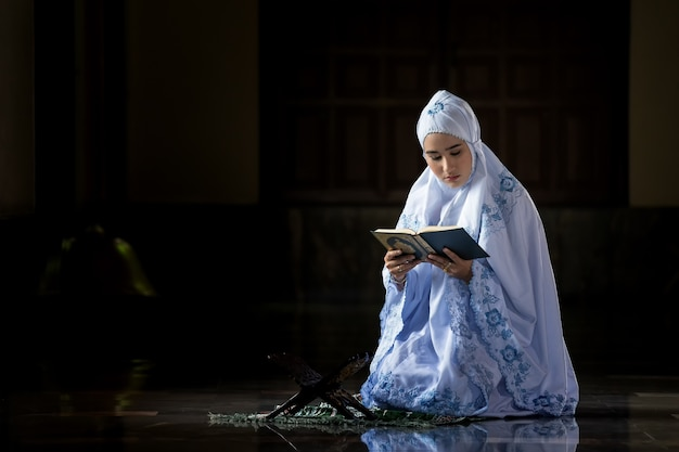 Muslim women wearing white shirts doing prayer according to the principles of islam. Premium Photo