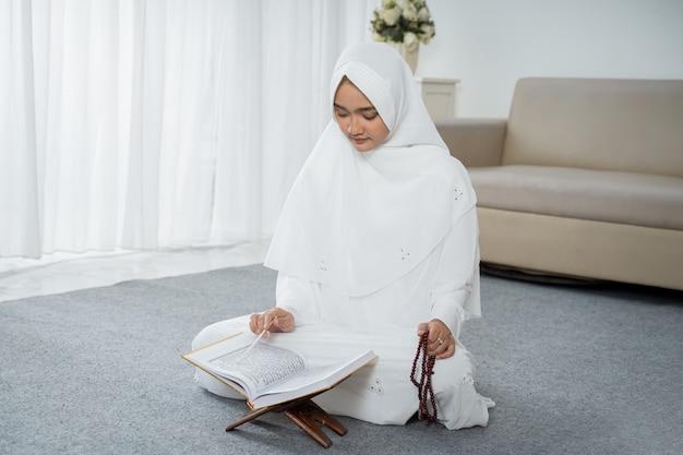 白の伝統的な服で祈るイスラム教徒の若い女性 Premium写真