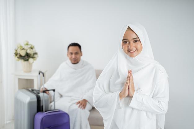 ウムラの前に彼女の夫の前に立っているイスラム教徒の若い女性 Premium写真
