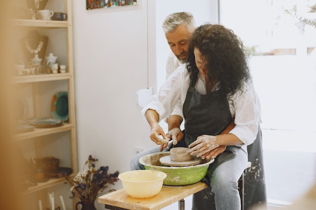 Mutual creative work. adult elegant couple in casual clothes and aprons. people creating a bowl on a pottery wheel in a clay studio. Free Photo