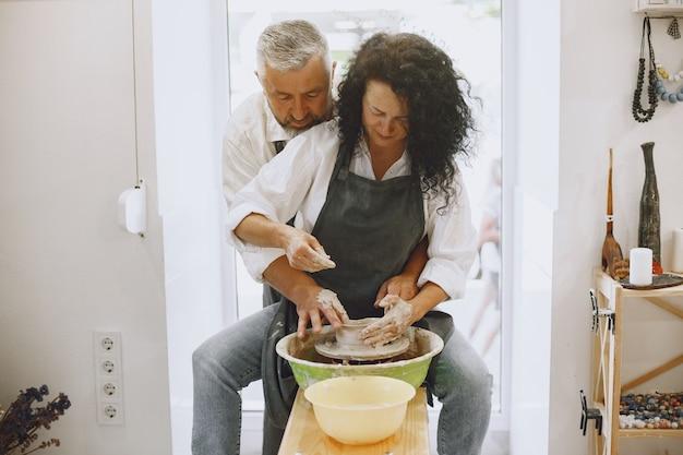 Совместная творческая работа. взрослая элегантная пара в повседневной одежде и фартуках. люди создают чашу на гончарном круге в глиняной студии. Бесплатные Фотографии