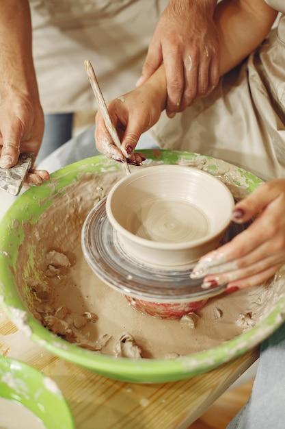 Совместная творческая работа. руки создают чашу на гончарном круге в глиняной студии. Бесплатные Фотографии