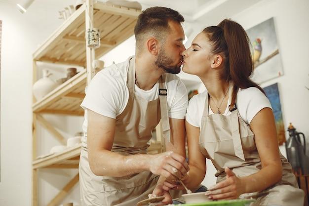 Совместная творческая работа. молодая красивая пара в повседневной одежде и фартуках. люди создают чашу на гончарном круге в глиняной студии. Бесплатные Фотографии