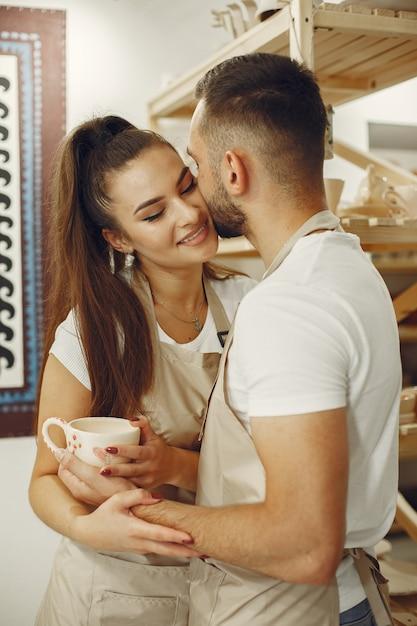 Совместная творческая работа. молодая красивая пара в повседневной одежде и фартуках. люди держит керамическую кружку. Бесплатные Фотографии