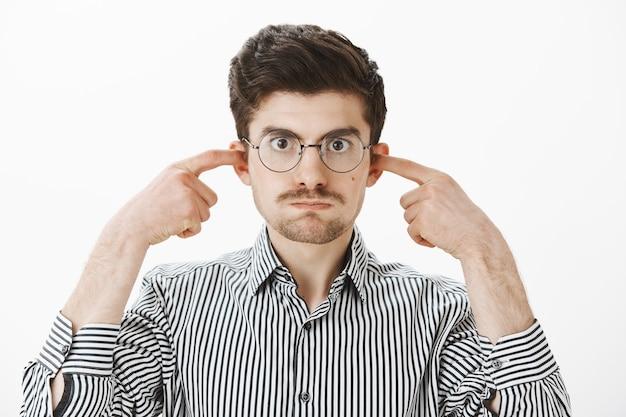 I miei minuti colpi dai tuoi discorsi. infastidito stufo ragazzo caucasico con gli occhiali, trattenendo il respiro e chiudendo le orecchie con le dita indice, guardando infastidito e scontento del fastidioso rumore sul muro grigio Foto Gratuite