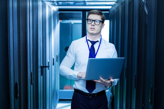 私の職業。データセンターでの作業中に彼のラップトップを保持しているインテリジェントな若年労働者 Premium写真