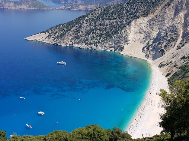Myrtos beach circondata dal mare sotto la luce del sole in grecia Foto Gratuite