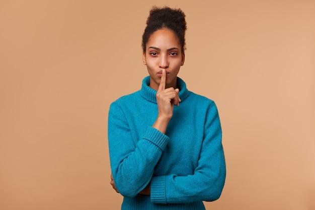 Misteriosa signorina afroamericana, dimostra un gesto di silenzio, tenendo un dito indice vicino alla bocca chiede di mantenere la privacy, il segreto, la calma, la calma. isolato. Foto Gratuite