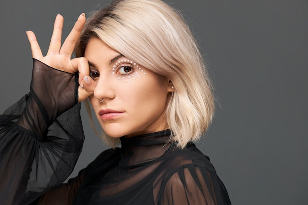 Mysterious beautiful young caucasian female with artistic bright make up and nose ring wearing trendy transparent blouse with enigmatic look, making gesture with fingers at her eye Free Photo