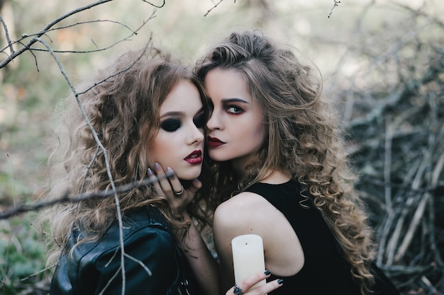 Mysterious witches posing with a candle Free Photo