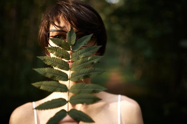 短いブルネットの髪と黒い瞳が森の中でポーズをとって、大きな緑の葉で顔を覆い、野生の自然を楽しんでいる謎の若い女性 無料写真