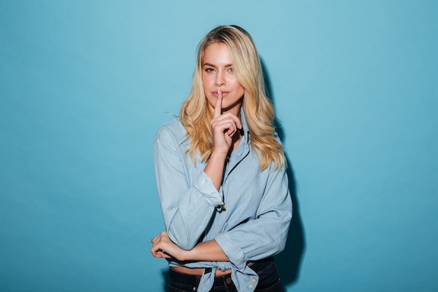 Mystery blonde woman in shirt showing silence gesture Free Photo