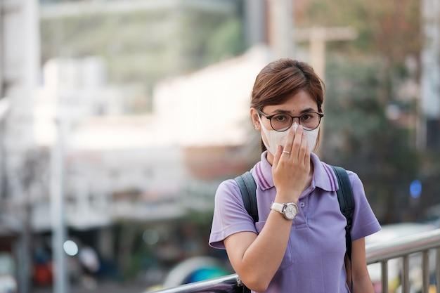 Молодая азиатская женщина, носящая респираторную маску n95, защищает и фильтрует pm2.5 (твердые частицы) от движения и пыли города. здравоохранение и концепция загрязнения воздуха Premium Фотографии