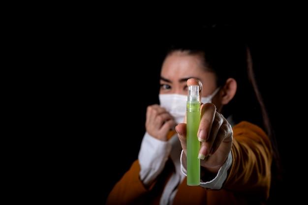 Предприниматель молодой женщины азии надевает респираторную маску n95 рукой, которая наносит спиртовой спрей из пластиковой бутылки или антибактериальные средства для предотвращения распространения микробов на черной поверхности Premium Фотографии