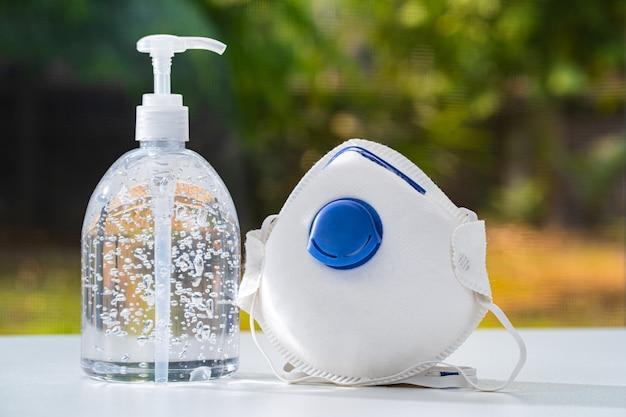 Антисептический гель для рук и маска n95 на белом столе Premium Фотографии