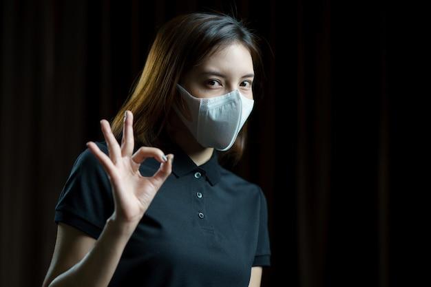 Женщина нося респираторную защитную маску n95 показывая знак руки одобренный. Premium Фотографии