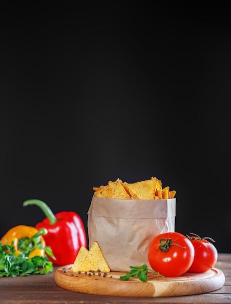 Чипсы начо в пакете с петрушкой и помидорами Premium Фотографии