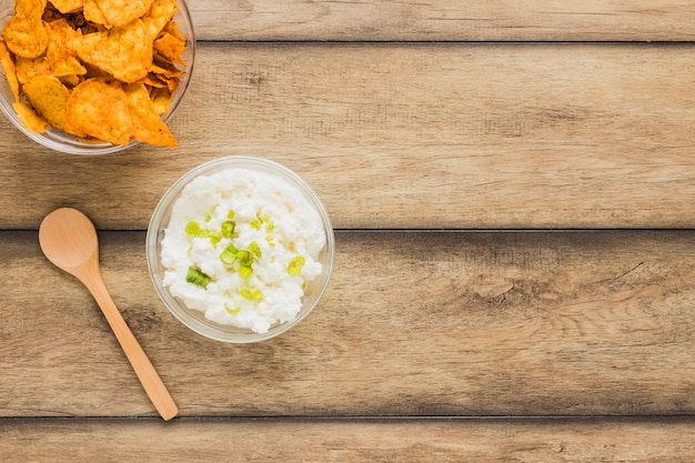 Nachos chips with cheese dip bowl and wooden spoon on table Free Photo