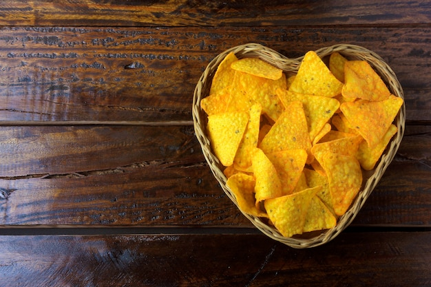 Nachos corn chips placed in basket with heart shape on wooden table, space for text Premium Photo