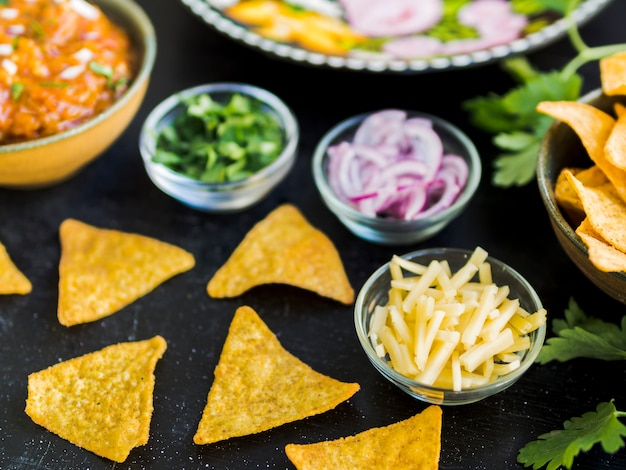 Nachos and cups with vegetables and potatoes Free Photo
