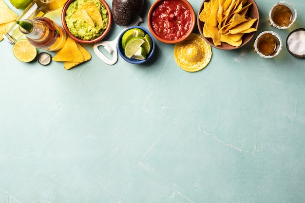 Nachos, guacamole, salsa and beer and tequila on blue background Premium Photo