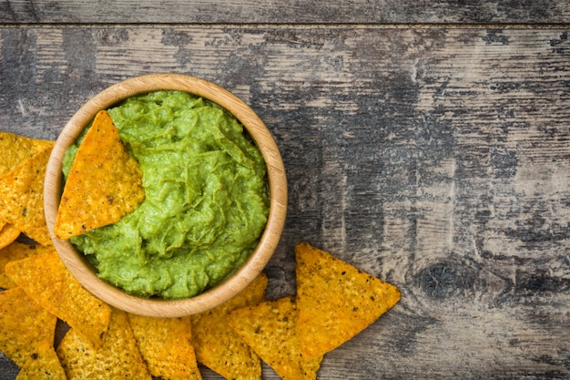 Nachos with guacamole on wooden table top view, copy space Premium Photo