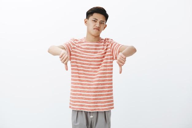Нет отрицательный отзыв. раздосадованный и недовольный привлекательный молодой азиатский мужчина в полосатой футболке показывает большие пальцы вниз, подняв голову с презрением, но не впечатлен Бесплатные Фотографии
