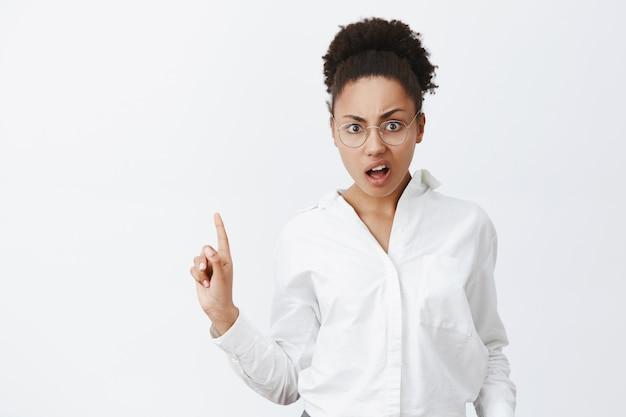 No, assolutamente no. ritratto di femminile dispiaciuta e arrabbiata attraente emotiva donna di pelle scura con i capelli ricci, gesticolando con il dito in segno di no o di rifiuto, in piedi sopra il muro grigio Foto Gratuite