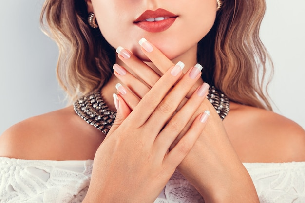 Nail art and design. beautiful woman wearing make-up and jewellery and showing her french manicure P