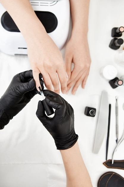 Nail artist in guanti applicando la mano di fondo sul mignolo. Foto Gratuite
