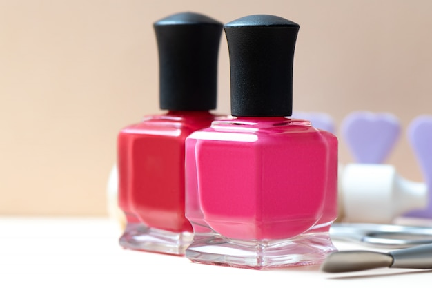 Nail polish bottles and manicure tools on a table. Premium Photo