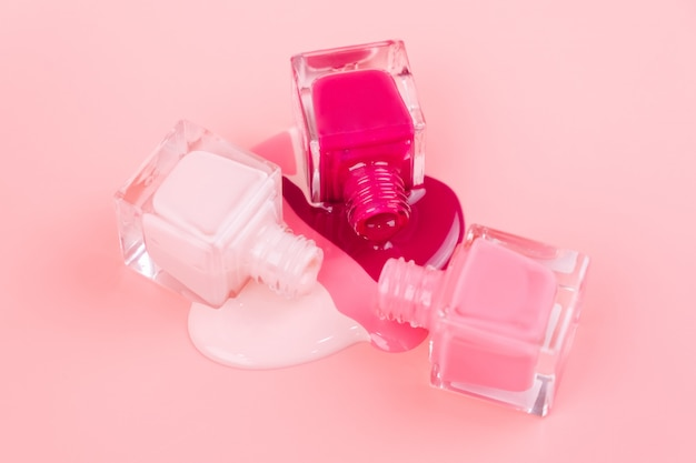 Nail polishes drip on a pink surface Premium Photo