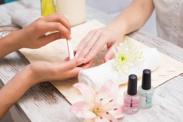 Nail technician giving customer a manicure Premium Photo