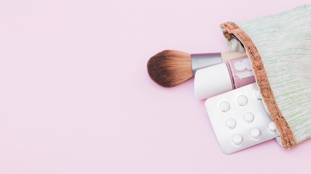 Nail varnish bottle; makeup brush and pills blister pack out from pouch against pink background Free Photo