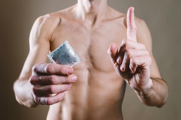 黒のジーンズを着た裸の魅力的な男性が腰にコンドームを持ち、もう一方の手は指で上向き Premium写真