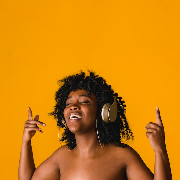 Naked black young female singing in headset in studio Free Photo