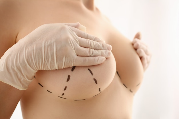 Naked female patient covering nipples with hands Premium Photo