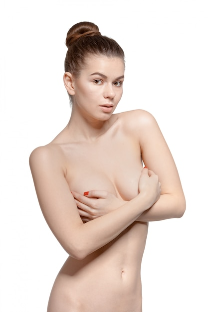 Naked girl who carefully verifies hands her breasts Premium Photo