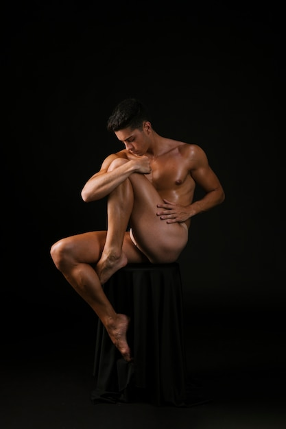 Naked guy embracing knee Free Photo