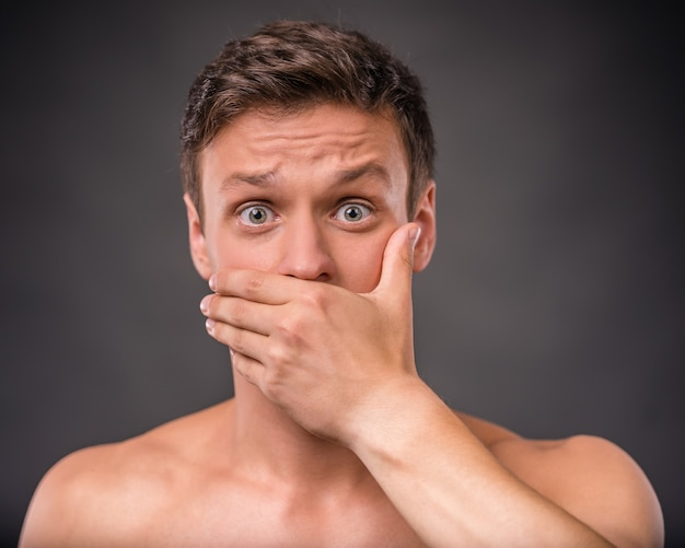 Naked man stands and covers his mouth with his hand. Premium Photo