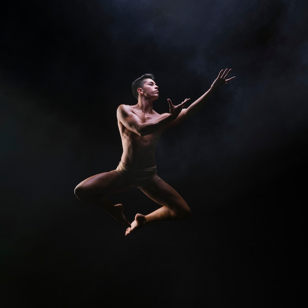 Naked muscled male jumping and raising hands Free Photo