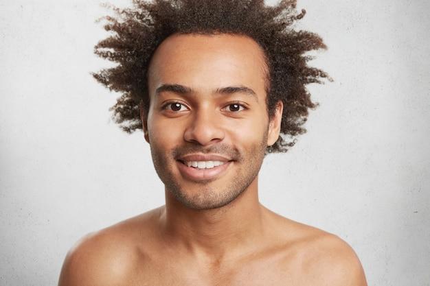 健康な暗い肌と巻き毛の裸の肯定的なアフロアメリカンの男性、優しく微笑む 無料写真