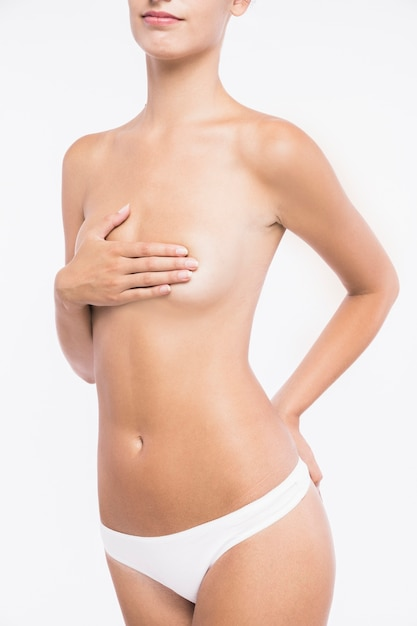 Naked young woman with hand on chest Free Photo