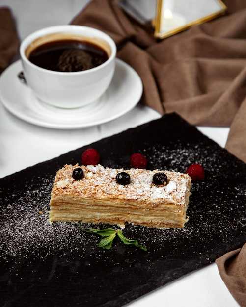 Napoleon cake piece garnished with sugar powder, served with black tea Free Photo