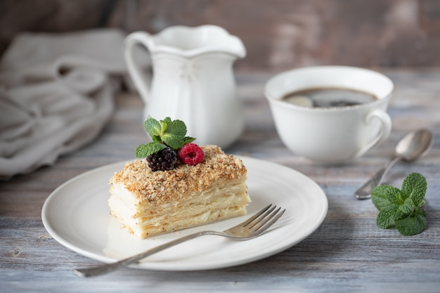 Napoleon dessert in a plate with berries and mint, with a cup of cappuccino on a wooden table. Premium Photo