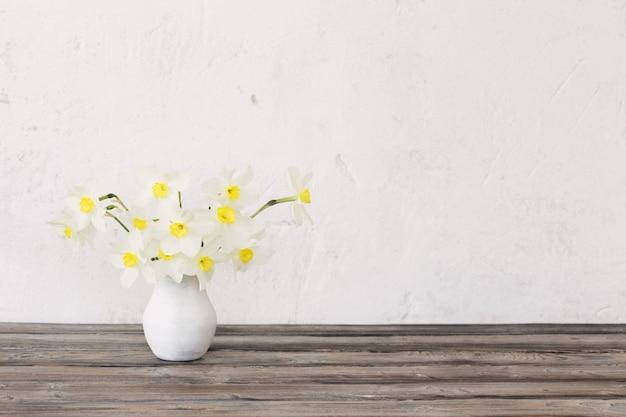 木製のテーブルの上に花瓶の水仙 Premium写真