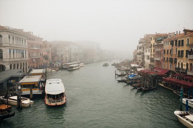 イタリア、ベニスの古いカラフルなレンガ造りの家に囲まれた狭い運河。 無料写真